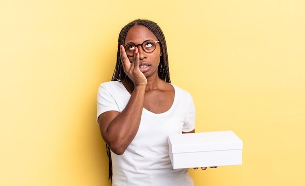 Sensazione di noia, frustrazione e sonno dopo un compito noioso, noioso e noioso, tenendo il viso con la mano e tenendo una scatola vuota