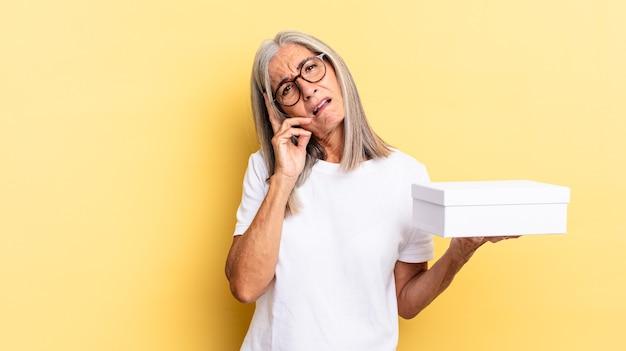Sensazione di noia, frustrazione e sonno dopo un compito noioso, noioso e noioso, tenendo il viso con la mano e tenendo in mano una scatola bianca