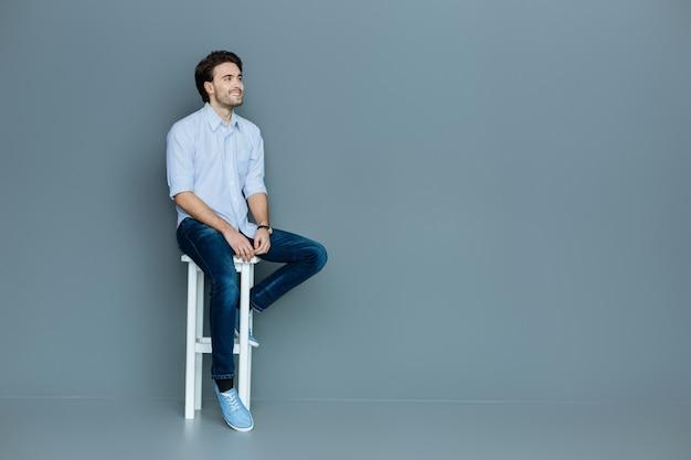 Sentirsi a proprio agio. gioioso giovane positivo seduto su uno sgabello e sorridente pur essendo di ottimo umore