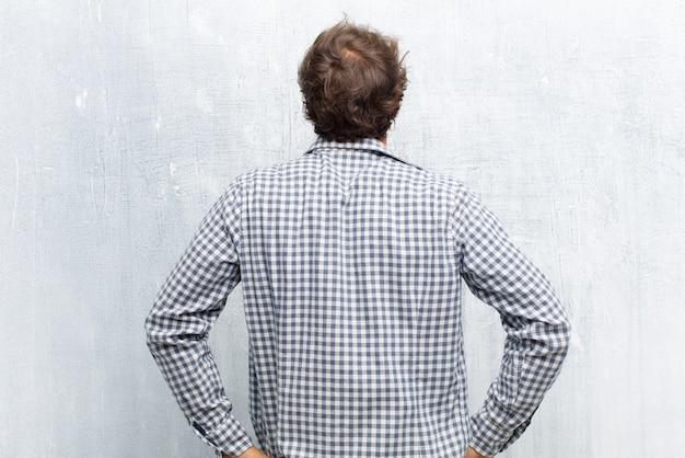 Sentirsi confusi o pieni o dubbi e domande, chiedersi, con le mani sui fianchi, vista posteriore