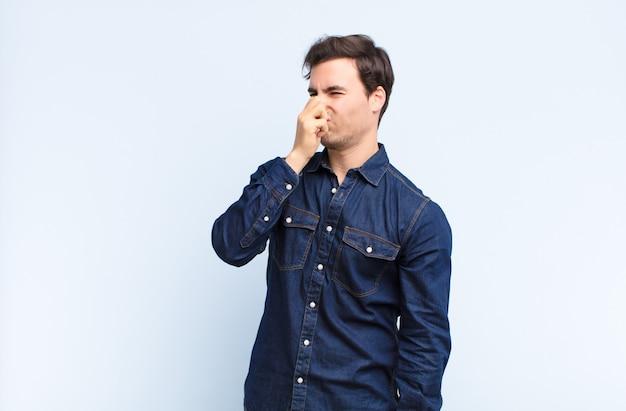 Sentirsi disgustati, trattenendo il naso per evitare di annusare un cattivo odore e un cattivo odore