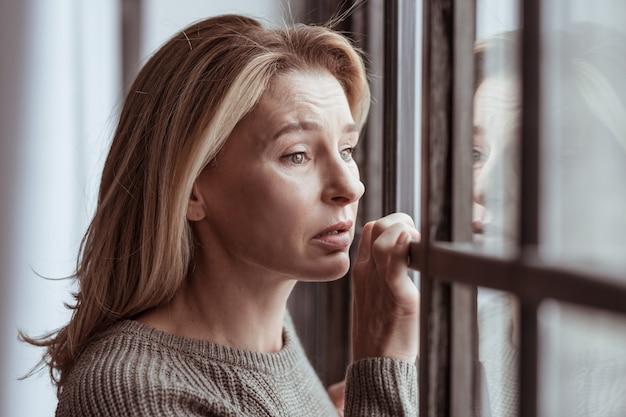 Sentirsi emotivi. donna dagli occhi azzurri che si sente estremamente emotiva vedendo un incidente d'auto dalla finestra