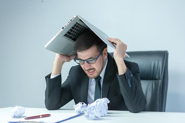 Sentirsi stremato. giovane frustrato che tiene gli occhi chiusi e sembra stanco mentre lavora fino a tardi al suo posto di lavoro.