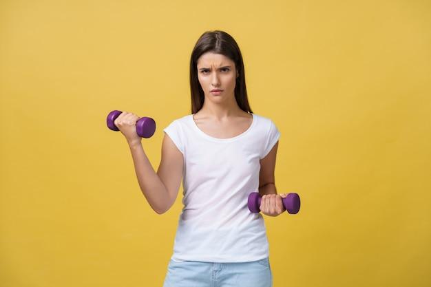 Sentirsi stremato. giovane donna frustrata in camicia bianca che si esercita con manubri e sguardo serio mentre in piedi isolato su sfondo giallo.