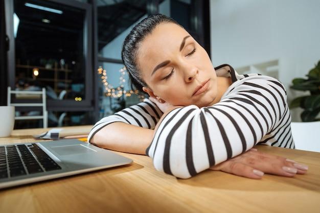 Sentirsi stremato. piacevole attraente donna che lavora sodo seduto alla scrivania e fare un pisolino pur essendo troppo esausto dal lavoro