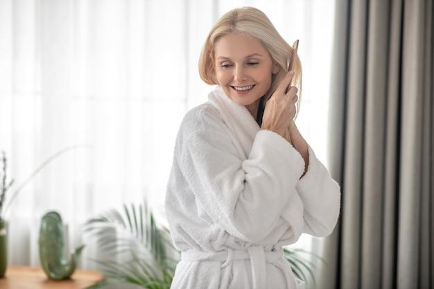 Sentirsi bene. adorabile donna che si spazzola i capelli e sembra rilassata
