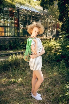 Sentirsi bene. giovane donna dai capelli ricci sentirsi bene in una giornata di sole sunny