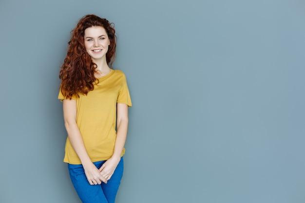 Sensazione di felicità. felice donna gioiosa positiva in piedi contro il muro e sorridente mentre esprime le sue emozioni