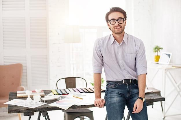 Sentirsi felice. uomo attraente contenuto sorridente e in piedi vicino al tavolo