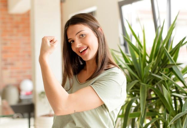 Sentirsi felice soddisfatto e potente flessione in forma e bicipiti muscolari che sembrano forti dopo la palestra