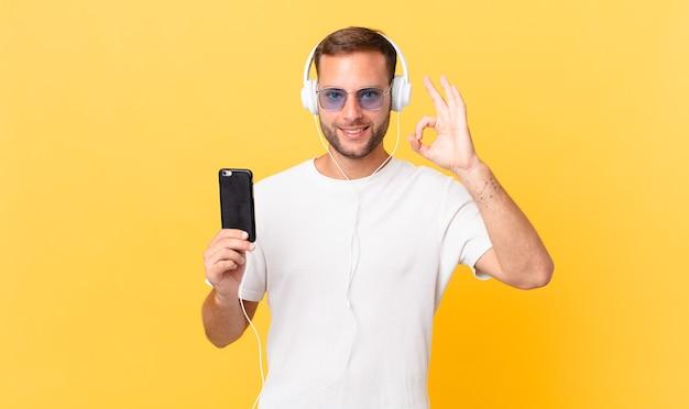 Sentirsi felici, mostrare approvazione con un gesto ok, ascoltare musica con le cuffie e uno smartphone