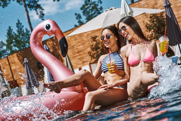 Sentendosi felici due giovani donne giocose e felici in costume da bagno che si divertono e bevono freddo