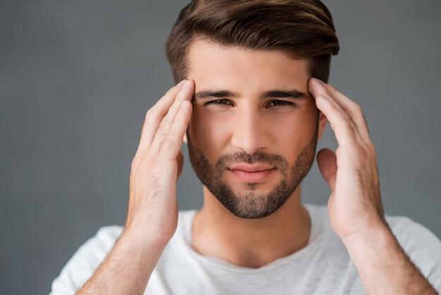 Sensazione di mal di testa. giovane depresso che si tocca la testa ed esprime negatività stando in piedi su uno sfondo grigio