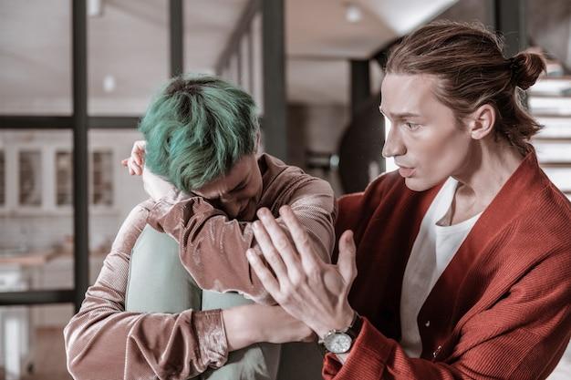 Sentirsi soli. moglie dai capelli verdi che si sente sola dopo un litigio nervoso con il giovane marito
