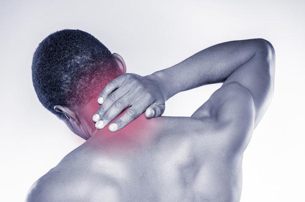 Sensazione di dolore al collo. vista posteriore di un giovane africano muscoloso che si tocca il collo mentre si trova su uno sfondo grigio