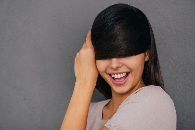 Sentirsi giocoso. bella giovane donna che copre gli occhi con i capelli e sorride