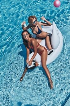 Sentirsi giocoso. vista dall'alto di due giovani donne attraenti in bikini che sorridono mentre galleggiano su un grande cigno gonfiabile