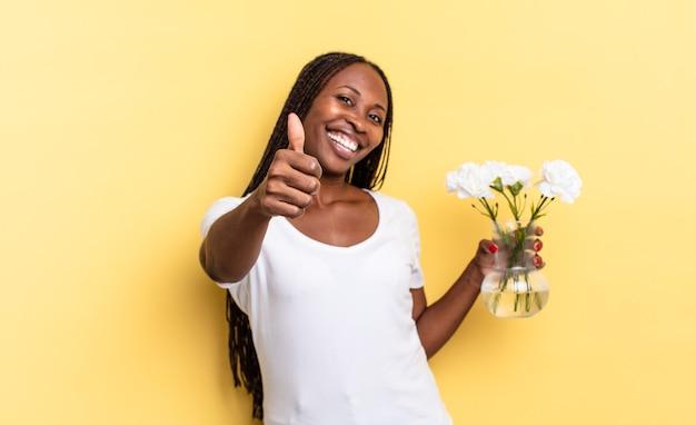 Sentirsi orgogliosi, spensierati, fiduciosi e felici, sorridere positivamente con il pollice in alto. concetto di fiori decorativi