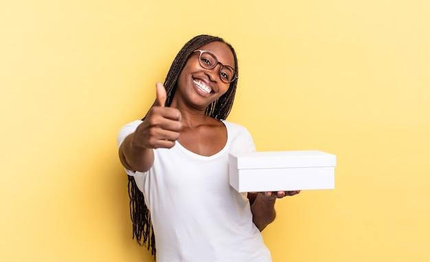 Sentirsi orgogliosi, spensierati, fiduciosi e felici, sorridere positivamente con il pollice in alto e tenere in mano una scatola vuota
