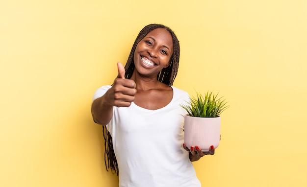 Sentirsi orgogliosi, spensierati, fiduciosi e felici, sorridendo positivamente con il pollice in alto tenendo in mano un vaso per piante