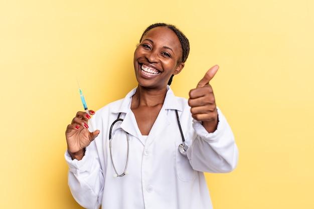 Sentirsi orgogliosi, spensierati, fiduciosi e felici, sorridere positivamente con il pollice in alto. medico e concetto di siringa