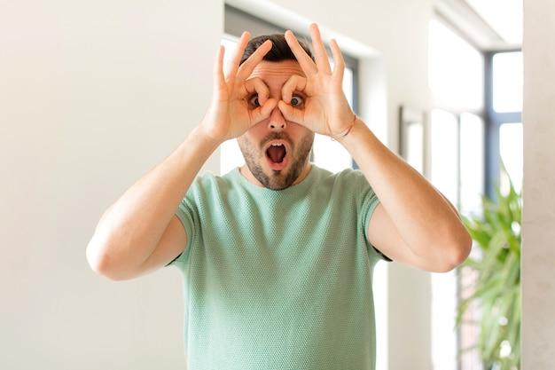 Sentirsi scioccato, stupito e sorpreso, tenendo gli occhiali con uno sguardo stupito e incredulo