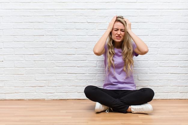 Sentirsi stressati e ansiosi, depressi e frustrati dal mal di testa, alzando entrambe le mani alla testa
