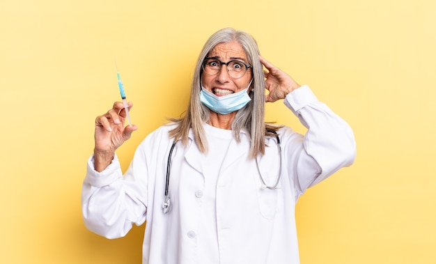 Sentirsi stressati, preoccupati, ansiosi o spaventati, con le mani sulla testa, in preda al panico per l'errore. medico e concetto di vaccino