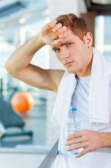Sensazione di stanchezza dopo l'allenamento. giovane stanco con un asciugamano sulle spalle che guarda la telecamera mentre tiene una bottiglia d'acqua e si tocca la fronte