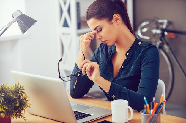 Sensazione di stanchezza e stress. giovane donna frustrata che tiene gli occhi chiusi e si massaggia il naso