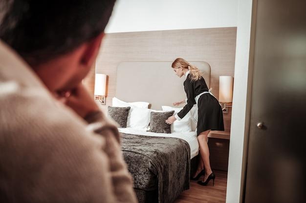 Sensazione di disagio. giovane cameriera d'albergo si sente a disagio mentre l'uomo la guarda lavorare