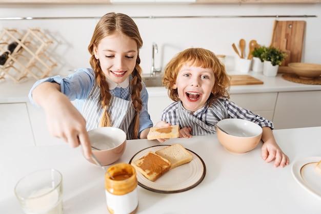 Sentire le vibrazioni. bambini fantastici e divertenti ottimisti che sembrano eccitati per il prossimo giorno mentre fanno colazione insieme e mangiano gustosi panini