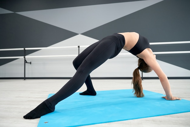 Adolescente femminile che pratica la posizione del ponte nello studio di danza