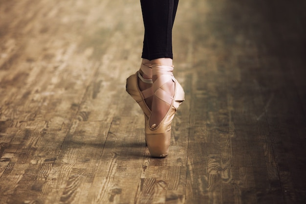 Piedi della ballerina in scarpe da ginnastica sul pavimento in legno parquet si chiudono in stile retrò