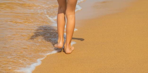 Piedi di un bambino che corre lungo la spiaggia.