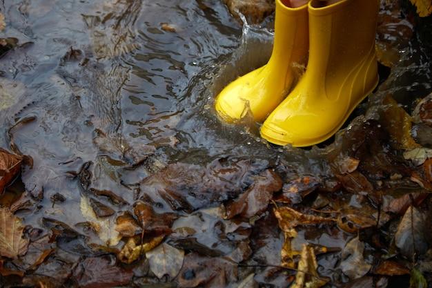 Piedi del bambino in stivali di gomma gialli che salta nella pozzanghera in autunno.