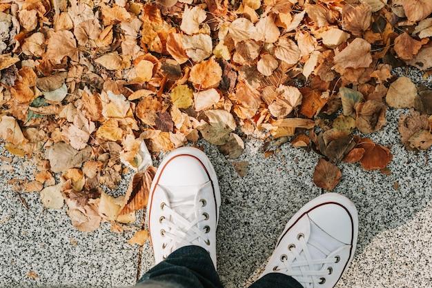 Piedi di una ragazza in jeans e scarpe da ginnastica bianche sul marciapiede con foglie di autunno gialle