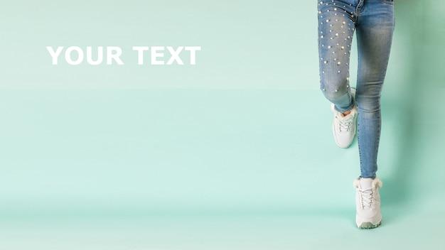 Piedi di una ragazza in jeans e scarpe da ginnastica calde bianche contro un muro blu. stile sportivo invernale.