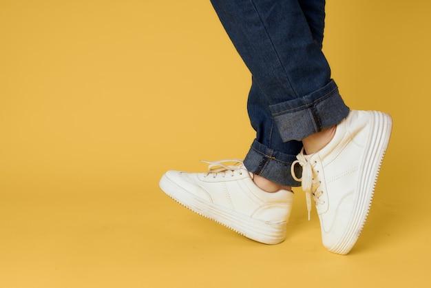 Piedi jeans moda scarpe sneakers bianche sfondo giallo