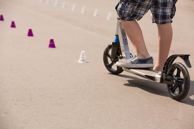 Piedi di un bambino con scarpe da ginnastica in scooter in una giornata di sole