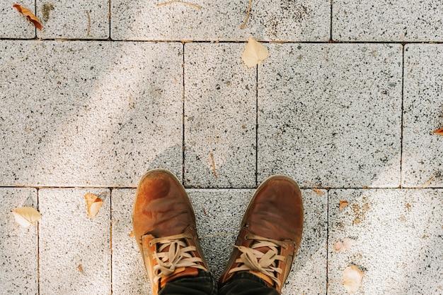 I piedi di un uomo con stivali marroni sul marciapiede di granito grigio