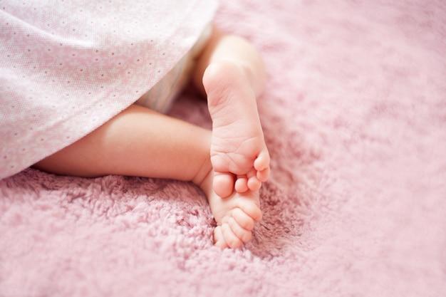 Piedi della neonata su pinkblanket dita sul piede cure materne amore e abbracci familiari tenerezza gambe della neonata