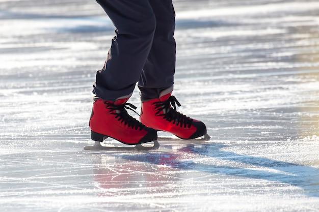 Piedi in pattini rossi su una pista di pattinaggio. hobby e tempo libero. sport invernali