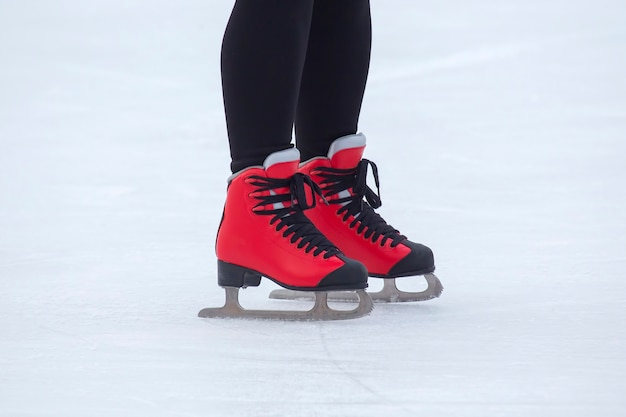 Piedi in pattini rossi su una pista di pattinaggio sul ghiaccio. hobby e tempo libero. sport invernali