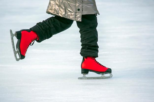Piedi in pattini rossi su una pista di pattinaggio sul ghiaccio. hobby e sport. vacanze e attività invernali.