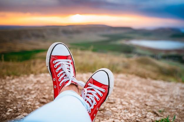Piedi in scarpe da ginnastica rosse sul bordo di una scogliera all'alba che si affacciano su un fantastico paesaggio con valli a