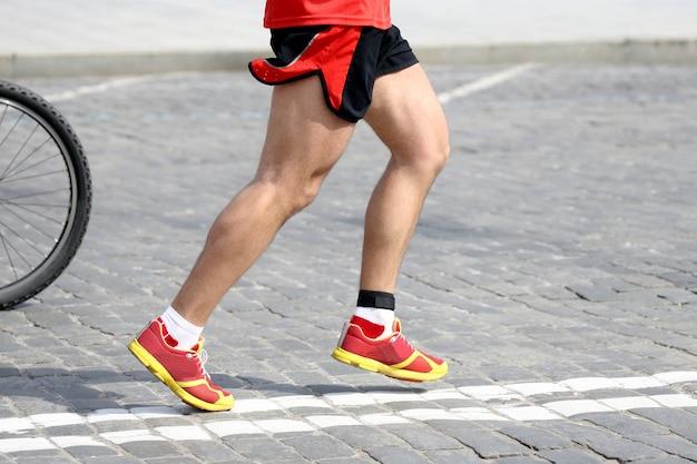Piedi che corrono atleta sul percorso