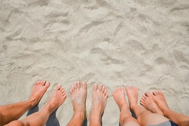 Piedi sulla sabbia di persone felici in riva al mare in viaggio nella natura