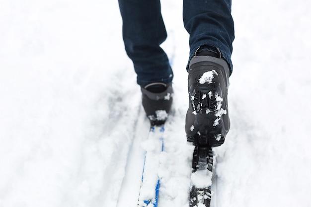 Piedi di uno sciatore con scarponi da sci sugli sci di fondo.