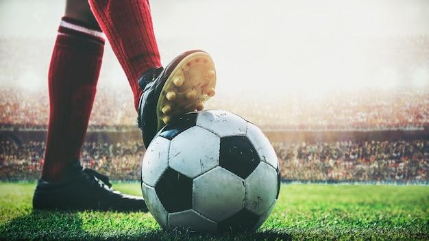 I piedi del calciatore calpestano il pallone da calcio per il calcio d'inizio allo stadio